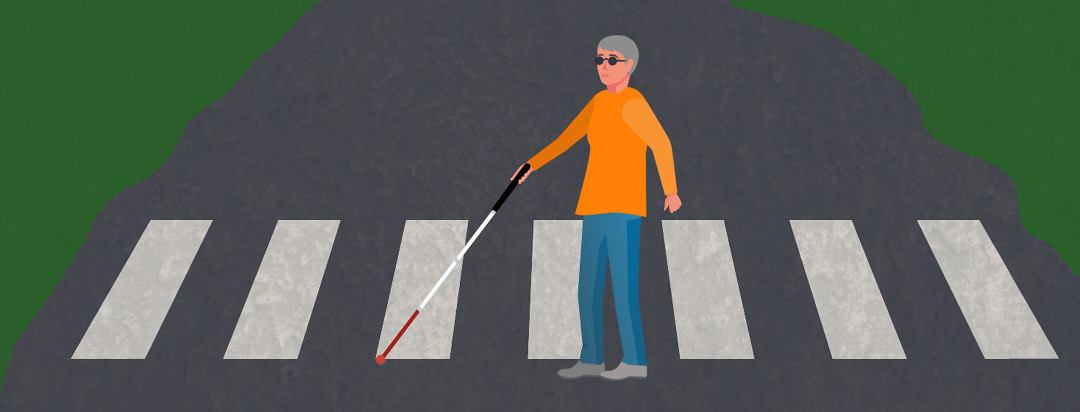 A woman crossing a quiet street with a white cane and dark glasses.