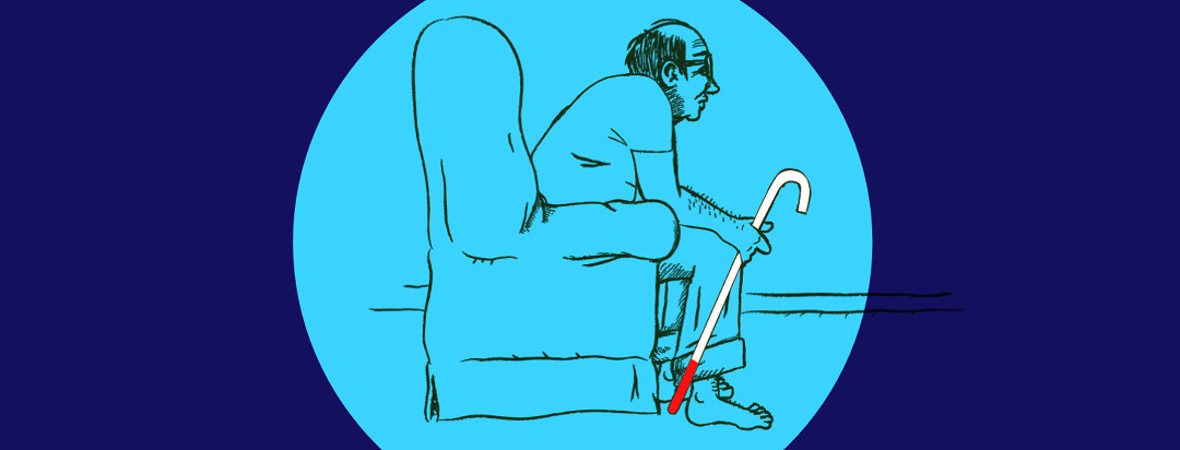 A senior man sitting alone in a chair at home, staring ahead and contemplating the future. He is holding a cane used for stability and impaired vision recognition.
