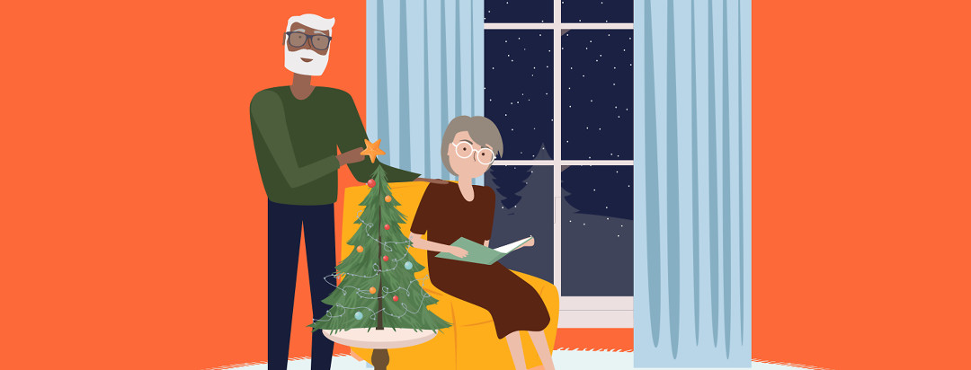 A man wearing glasses is helping to put the star on a tabletop Christmas tree. A woman sits in a recliner next to him with a large book.