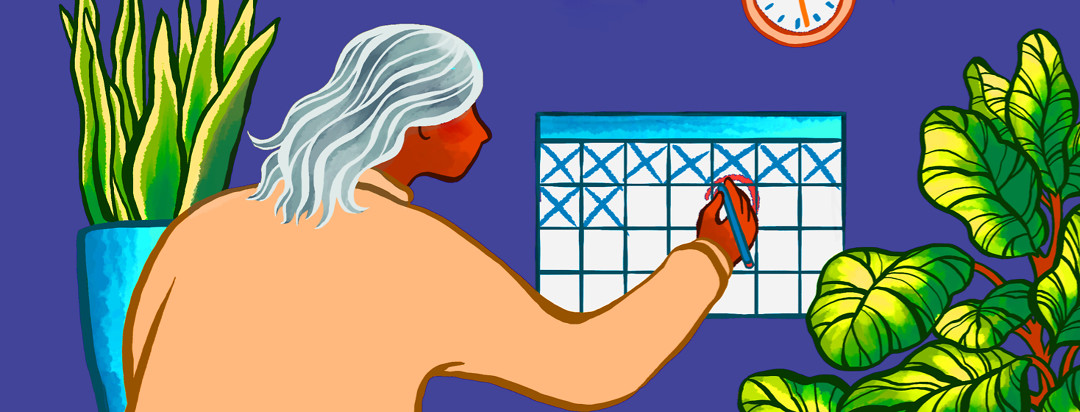 A woman with grey hair marks her calendar for an important monthly appointment.