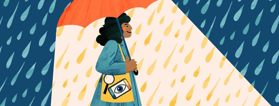 A smiling woman holding a bag full of vision assistive devices walks through the rain with an umbrella. The sky and rain around her are dark but the umbrella emits a beam of positive light.