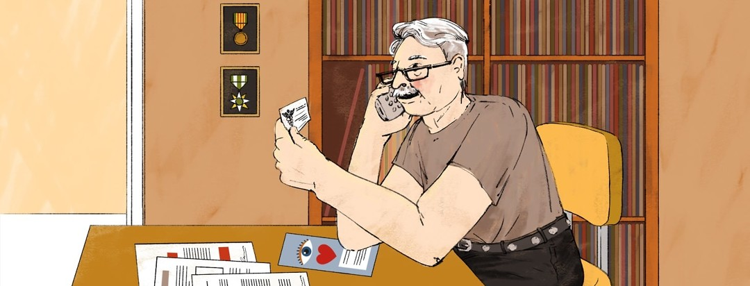 An older man talks on a telephone while looking at a doctor's business card. On the table he is sitting at are papers with signatures and a brochure featuring an eye and a heart. Behind him on the wall are stacks of records on shelves next to two war medals hanging on the wall.
