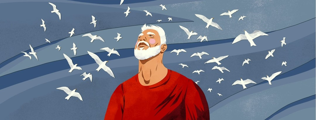 A man looks up toward the sky, which is full of flying seagulls.