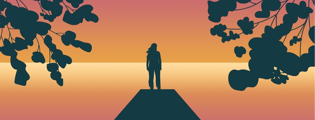 A person stands in silhouette at the end of a pier, facing the sunset on an ocean. Framing the image are silhouettes of flowering trees.