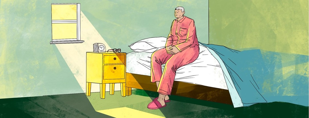 A person sits in their pajamas on the edge of a bed with their eyes closed. Sun is shining through a window forming a bright patch on the ground.