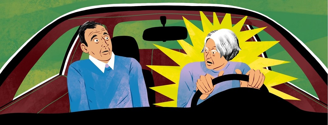 An older couple are in a car, with the woman driving. She looks angry and explodes at her partner sitting in the passenger seat, who leans back in surprise.