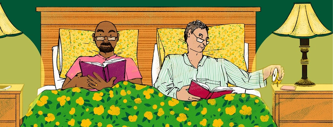alt=Two men read in bed. One is checking the time on an analog clock.