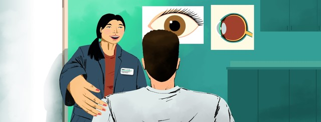 A woman with a name tag welcomes a man into an office that has anatomical eye posters on the walls.