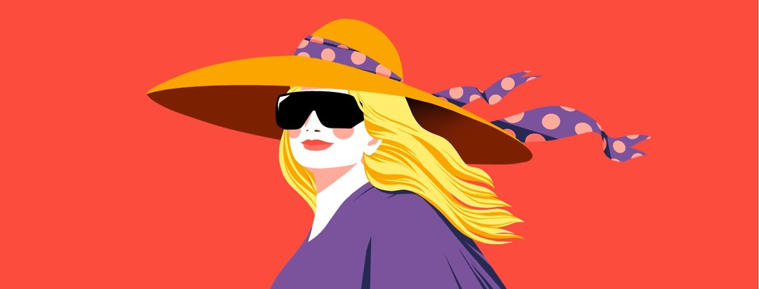 A smiling woman in a bright space is wearing a large sun hat with a ribbon blowing in the wind, and large, dark cataract sunglasses.