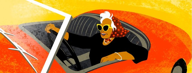 An older woman wearing a kerchief is smiling and driving a classic convertible.