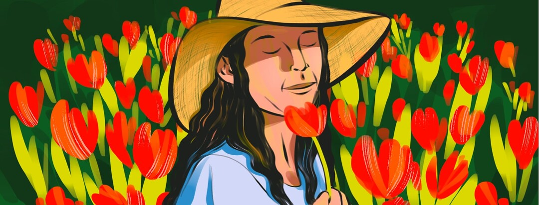 alt=A woman in a sunhat closes her eyes and smells a flower she is holding, while standing in a field of red flowers.