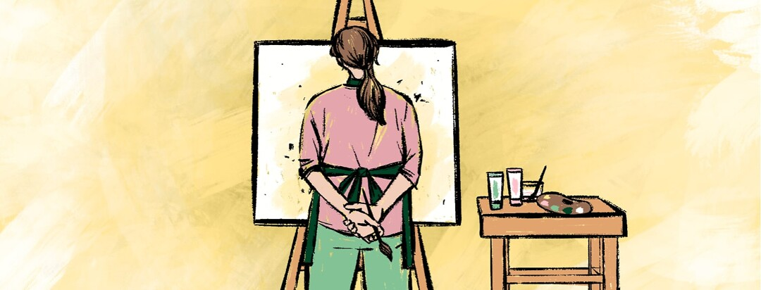 alt=A woman stands in front of a painted canvas on an easel next to a table with paints and a palette.