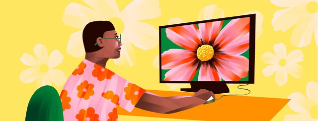 alt=a woman uses a computer with a large screen displaying a flower close-up
