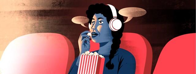 alt=A woman wearing headphones eats popcorn in a movie theater