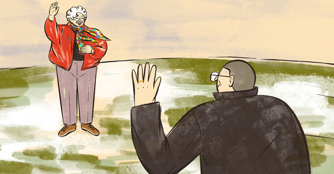 alt=an older woman in brightly colored clothes to match her colorful scarf waves to her approaching husband.