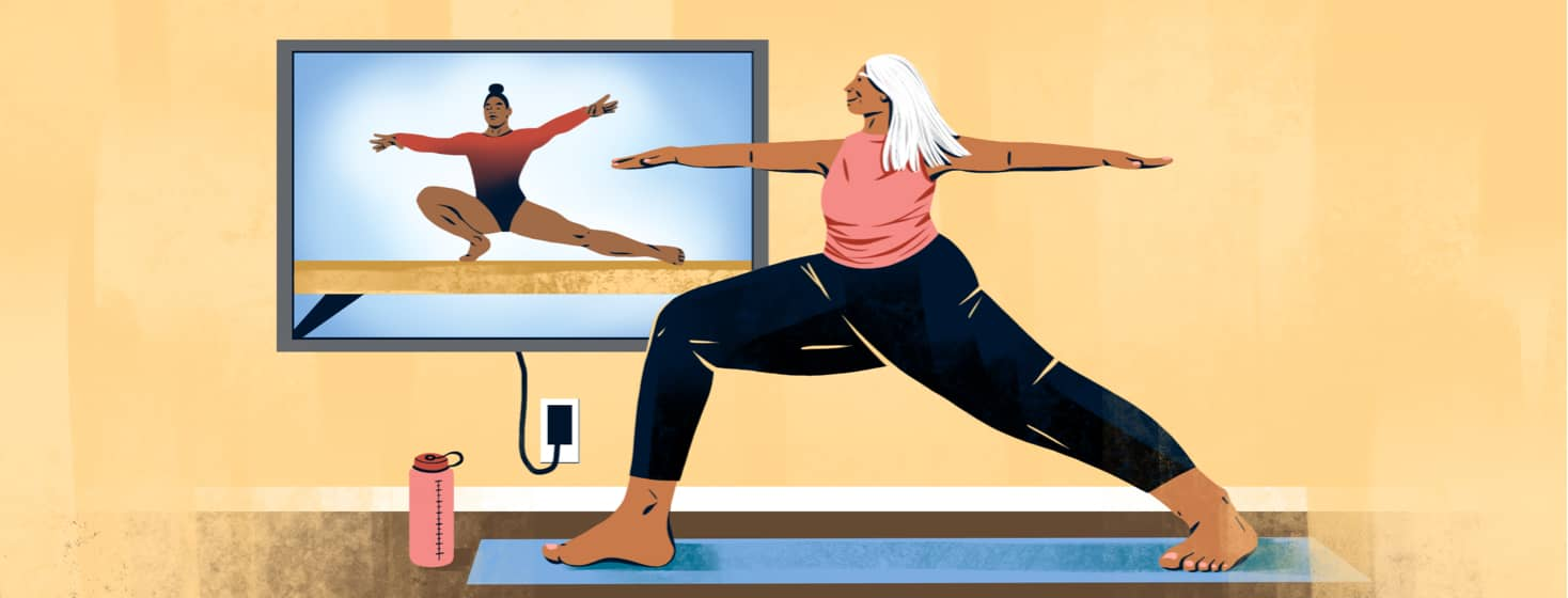 alt=an older woman does a warrior pose in front of a tv showing a gymnast doing a similar move on a balance beam.